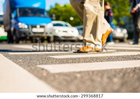 Sunny day in a city, pedestrians crossing the road. View from the level of asphalt - stock photo