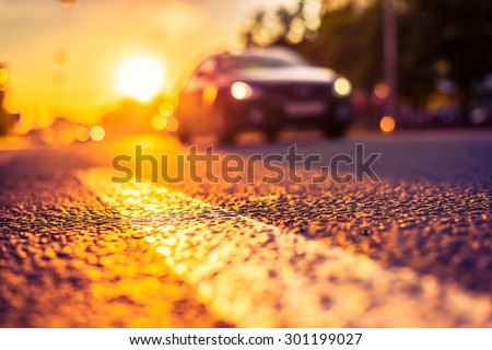 Sunny day in a city, view of the approaching car at the level of the dividing line. Image in the orange-purple toning - stock photo