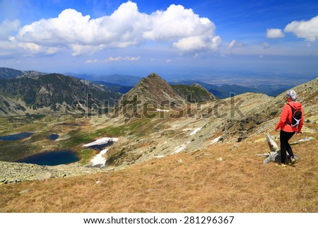 Sunny day of summer with hiker admiring beautiful mountains and lakes from above - stock photo