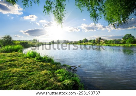 Sunny day on a calm river in summer - stock photo