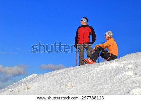 Sunny day on the mountain and a pair of hikers resting on the snow - stock photo