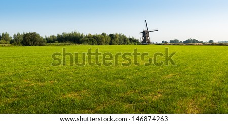 Sunny Dutch landscape in summertime with green grass and an historic mill. - stock photo