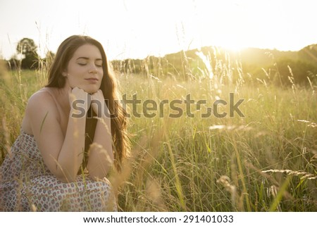 Sunny field. Beautiful young woman enjoying the sun rays shining down on lovely field. - stock photo