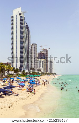SUNNY ISLES BEACH, USA - AUG 17, 2014: people enjoy the Jade beach in Sunny Isles Beach, USA. Jade Beach and Ocean condomium were completed in 2009 with a elevation of 549 feet. - stock photo