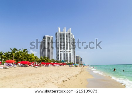 SUNNY ISLES BEACH, USA - AUG 17, 2014: people enjoy the Jade beach. Jade Beach and Ocean were completed in 2009 with a elevation of 549 feet located at 170th Street at Sunny Isles Beach, USA. - stock photo