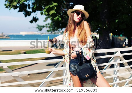 Sunny lifestyle fashion portrait of young stylish hipster woman walking on the street, wearing trendy outfit, hat, kimono, drinking tasty smoothie, smiling enjoy her weekends, travel with backpack - stock photo
