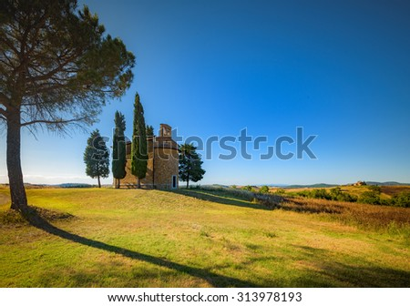 Sunny light of the setting sunset on Tuscan chapel in Val d'Orcia. - stock photo
