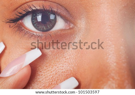 sunny macro photo of a mulatto female eye and fingers - stock photo