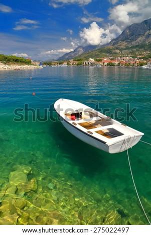 Sunny marina with traditional wooden boat inside Makarska harbor, Croatia - stock photo