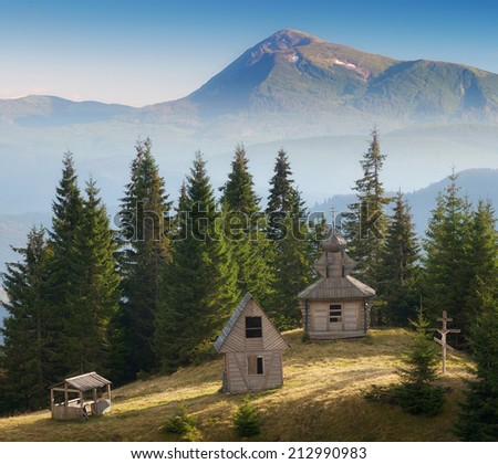 Sunny meadow with old wooden church. Mountain landscape with religious buildings - stock photo