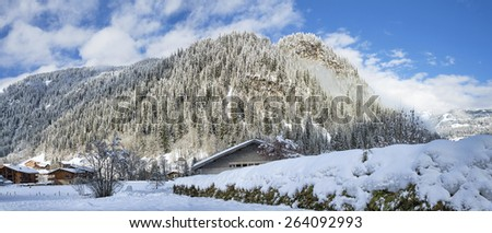 Sunny morning at winter Alpine village with forest and mountains background - stock photo