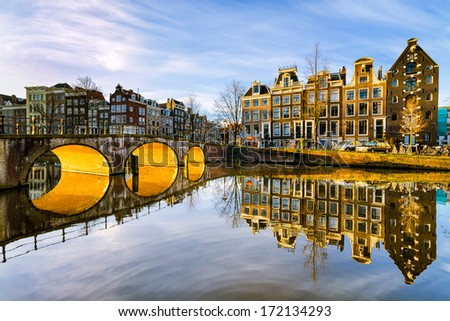 Sunny morning on a canal in Amsterdam, Netherlands with the sun shining below an arch bridge - stock photo