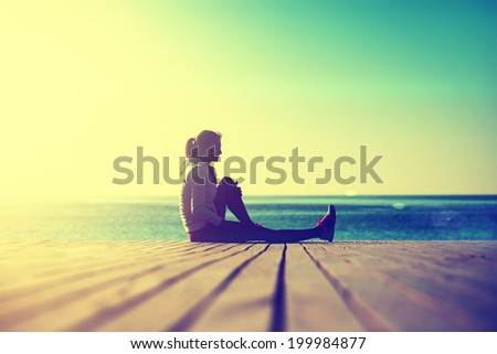 Sunny morning on the beach, athletic woman resting after stretching exercise at the morning training on the beach - stock photo