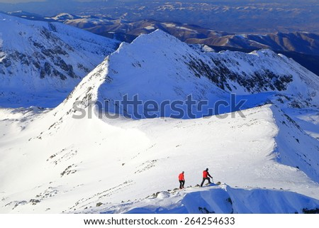 Sunny mountain ridge and couple of remote hikers in winter - stock photo