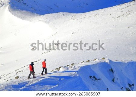 Sunny mountain ridge with hikers carefully walking on the snow - stock photo