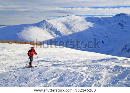 Sunny mountains with ski mountaineer traversing a white slope in winter - stock photo