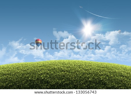 Sunny natural summer background with grassy hill and clear blue sky, balloons and aeroplane - great copy-space for posters, cards or banners - stock photo