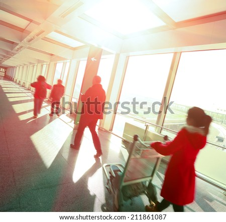 Sunny on passengers in modern airport interior glass wall aisle windows of people - stock photo