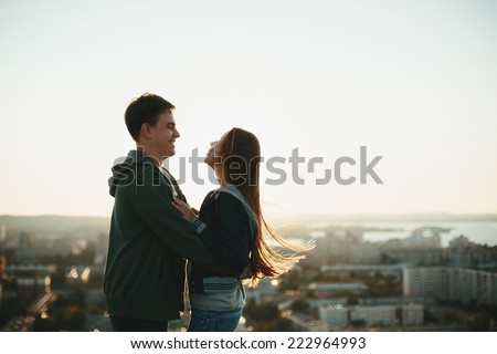 Sunny outdoor portrait of young happy stylish couple hugging on the roof at sunset. Man and woman laughing. - stock photo