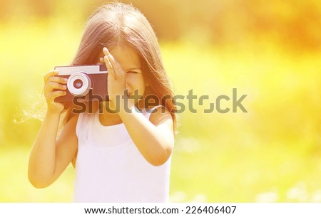 Sunny portrait child with old retro vintage camera outdoors - stock photo
