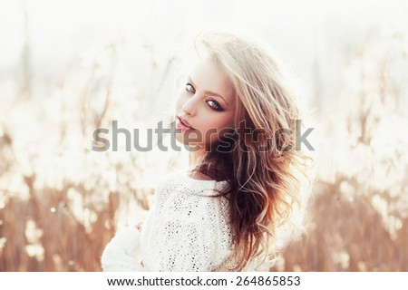 Sunny portrait of a beautiful young blonde girl in a field in white pullover, the concept of health and beauty - stock photo