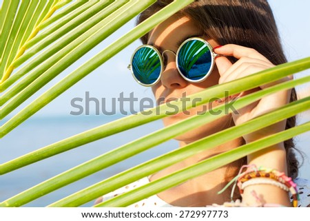 sunny portrait of a beautiful young girl in sunglasses - stock photo