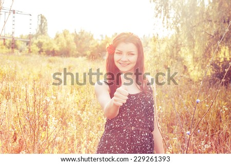 sunny portrait of a woman thumbs up with a poppy in her hair - stock photo