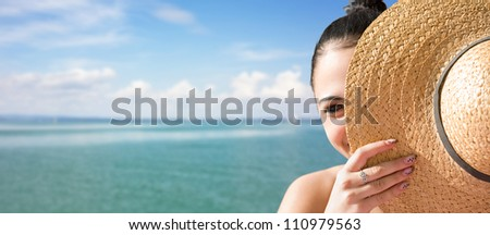 Sunny portrait of a young brunette relaxing at the beach. - stock photo
