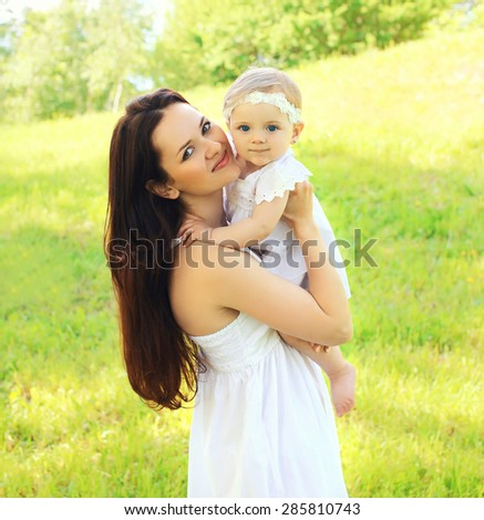 Sunny portrait of beautiful young mother and baby together on the nature - stock photo
