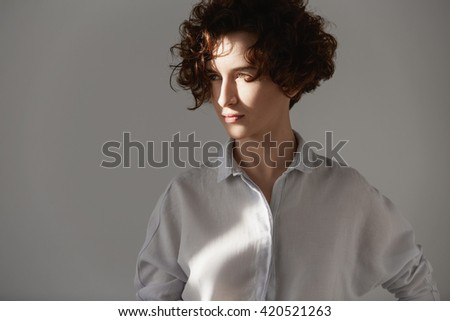 Sunny portrait of beautiful young woman with gorgeous brunette short curly hair, wearing trendy white shirt posing isolated against white concrete studio wall, looking away with thoughtful expression - stock photo