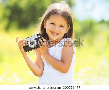 Sunny portrait of cute smiling little girl child with retro vintage camera in summer day - stock photo