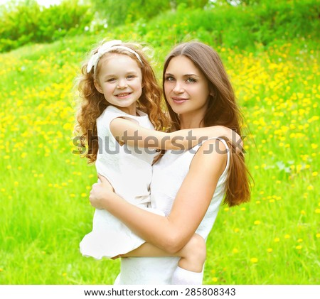 Sunny portrait of mother and daughter together having fun in summer day, mom with child outdoors - stock photo