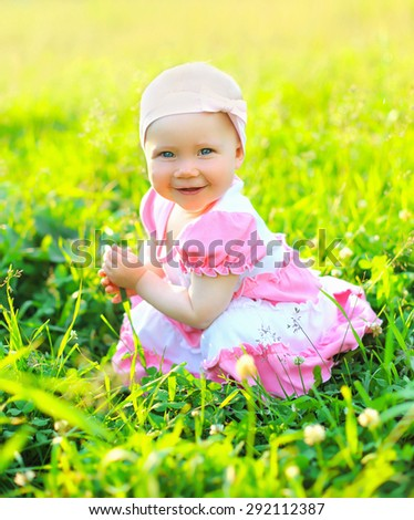 Sunny portrait of smiling child sitting on the grass in summer day - stock photo
