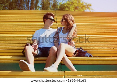 Sunny portrait young couple in love summer, stylish teenagers rest on the bench in city park - stock photo