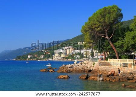 Sunny promenade and beach of a traditional resort by the Adriatic sea, Opatija, Croatia - stock photo