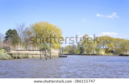 Sunny riverside with marshland and reeds. View from a boat to a river with little pier or jetty in springtime. - stock photo