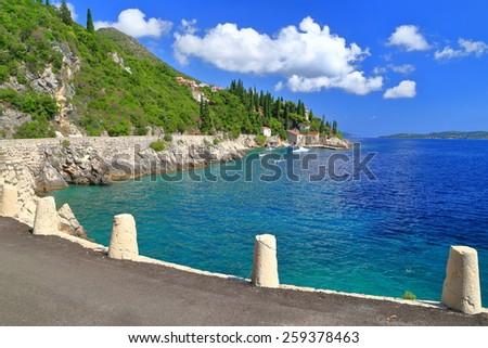 Sunny road along blue Adriatic sea, Trsteno, Croatia - stock photo