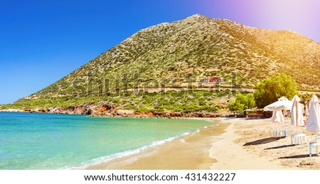 Sunny sandy Livadi beach in sea Bay of resort village Bali. Views of mountain, shore, washed by waves and sun loungers with parasols where sunbathing tourists. Bali, Rethymno, Crete, Greece - stock photo