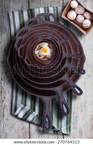 Sunny side up fried egg and mushrooms in a nested stack of old cast iron frying pans in a rustic kitchen, overhead view - stock photo