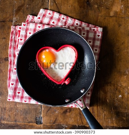 sunny-side up / fried egg in the shape of heart on a pan on a vintage wooden table - stock photo