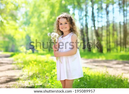 Sunny spring portrait of charming cute little girl with curly hair with a bouquet of yellow dandelions walk outdoors - stock photo