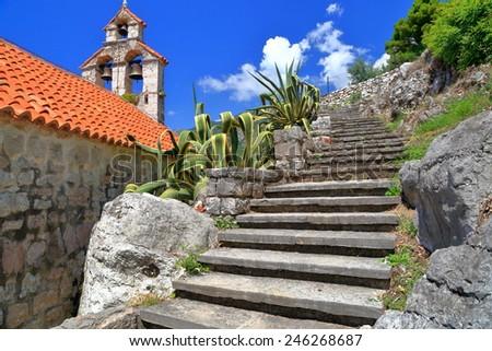 Sunny steps climb near orthodox church in Mediterranean area, Montenegro - stock photo