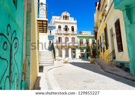 Sunny street in Havana sidelined by old colorful colonial buildings on a beautiful day with a clear blue sky - stock photo