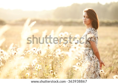 Sunny summer portrait of a beautiful young woman in a field - stock photo