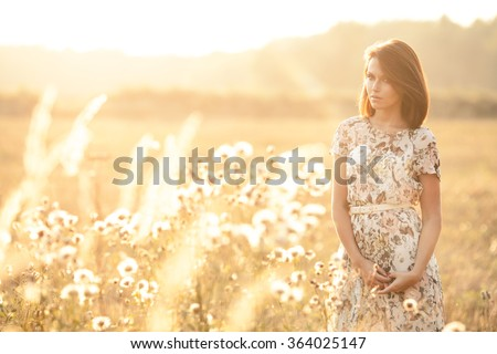 Sunny summer portrait of a beautiful young woman in the middle of a field - stock photo
