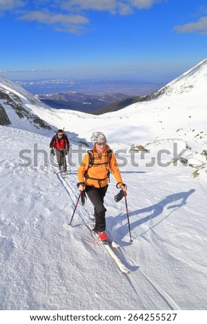 Sunny winter day with a team of hikers ascending on touring skies - stock photo