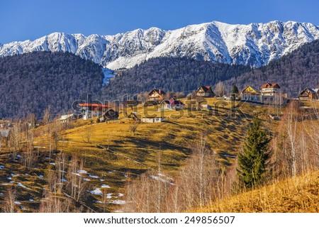 Sunny winter rural scenery with snowy Piatra Craiului mountain ridge and small village uphill in Pestera village, Brasov county, Romania. - stock photo