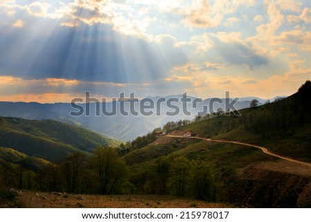 Sunrays in sunset over the high mountain dirt road and small house in bulgarian mountains  - stock photo