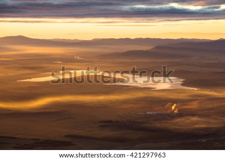Sunrise above a valley with a lake and small factory with smoking chimneys - stock photo