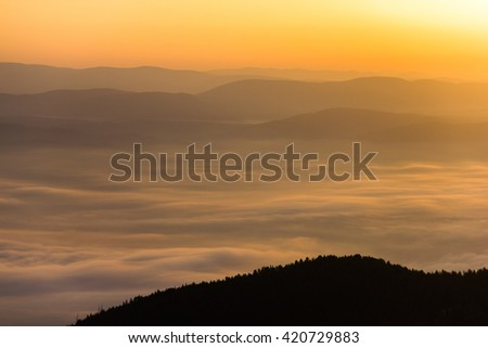 Sunrise above the clouds and silhouettes of mountain ridges - stock photo
